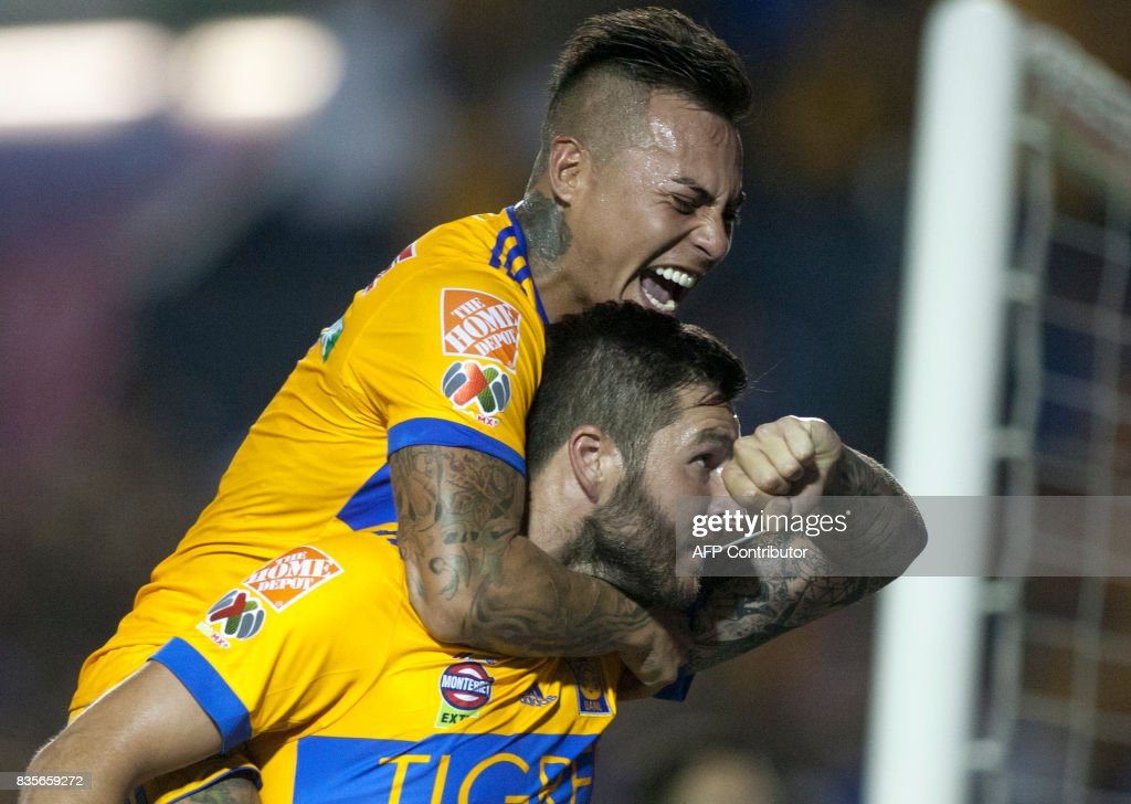 Tigres' Andre Pierre Gignac (R) celebrates with a teammate after scoring against Pumas during their Mexican Apertura 2017 tournament football match at the Universitario stadium in Monterrey, Mexico on August 19, 2017. / AFP PHOTO / Julio Cesar AGUILAR