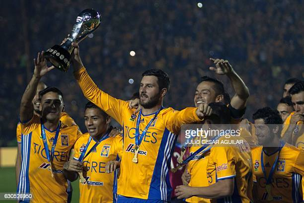 Tigres' Andre Pierre Gignac holds the trophy and celebrates teammates after defeating America during their Mexican Apertura 2016 tournament football...