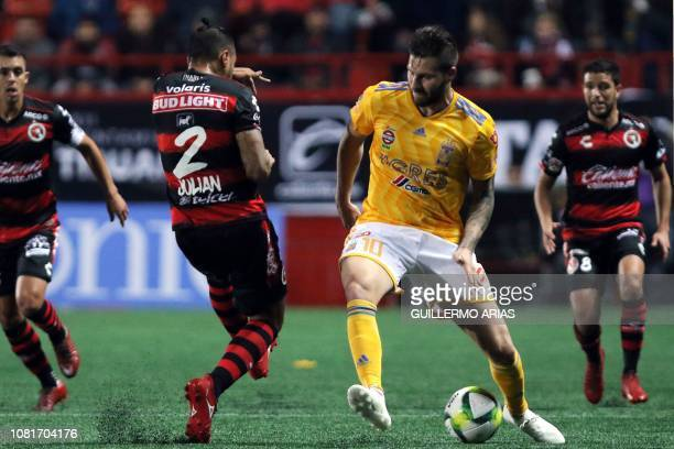 Tigres' Andrepierre Gignac vies for the ball with Tijuana's Julian Velazquez during the Mexican Clausura 2019 tournament football match between Club...