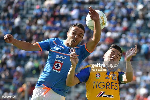 Tigres' defender Juninho vies for the ball with Cruz Azul's defender Omar Mendoza during their Mexican Clausura tournament football match at the Azul...