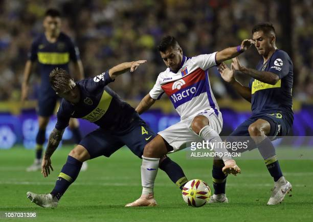 Tigre's defender Matias Perez Garcia vies for the ball with Boca Juniors' defender Julio Buffarini and midfielder Agustin Almendra during an...