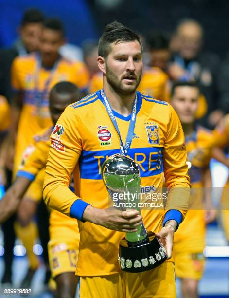 Tigres' French player Andre Pierre Gignac holds the trophy after winning the Mexican Apertura 2017 football tournament final match against Monterrey...