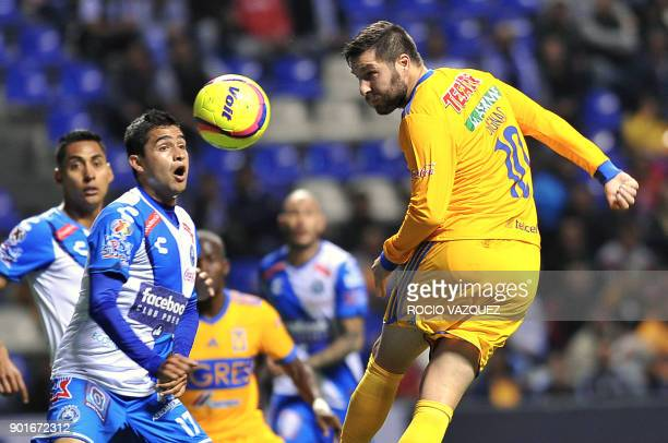 Tigres' French player AndrePierre Gignac heads the ball next to Alonso Zamora of Puebla during their Mexican Clausura tournament football match at...