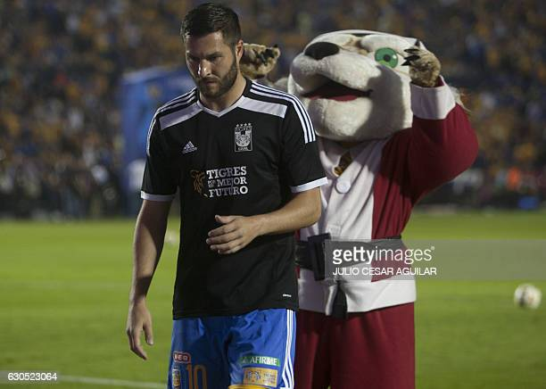 Tigres' player French footballer AndrePierre Gignac warms up followed by Tigres' mascot dressed as Santa Claus before the start of the 2016 Mexican...