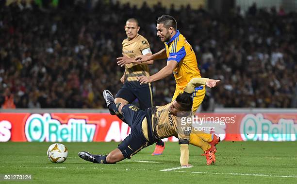Tigres's forward Andre Pierre Gignac vies for the ball with Pumas's defender Marcelo Alatorre during their Mexican Apertura tournament football final...