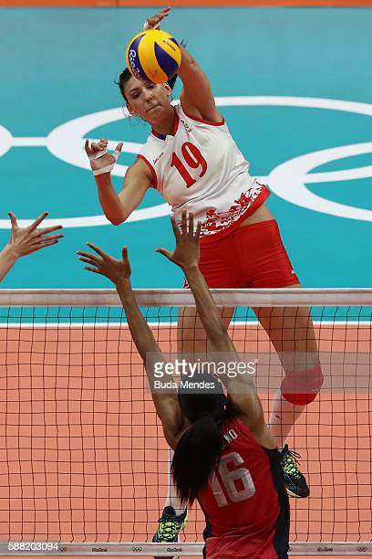 Tijana Boskovic of Serbia spikes the ball against Foluke Akinradewo of the United States during the women's qualifying volleyball match between the...