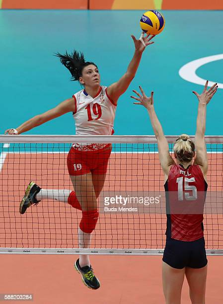 Tijana Boskovic of Serbia spikes the ball against Kimberly Hill of the United States during the women's qualifying volleyball match between the...