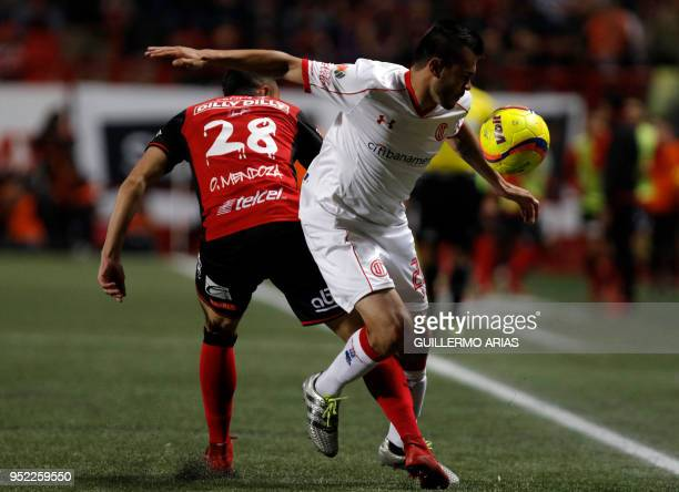 Tijuana's defender Omar Mendoza vies for the ball with Toluca's forward Argentinian Alexis Canelo during their Mexican Clausura 2018 tournament...