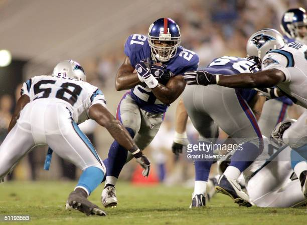 Tiki Barber of the New York Giants runs between Mark Fields and Brentson Buckner of the Carolina Panthers during a NFL game on August 19 2004 at Bank...
