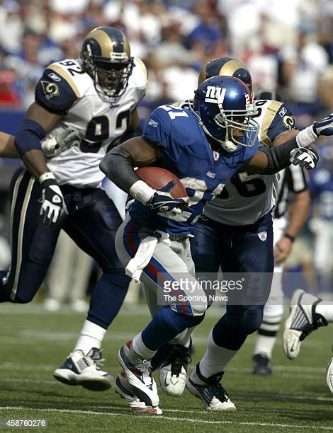 Tiki Barber of the New York Giants runs through the tackle during a game against the St Louis Rams on September 07 2003 at Giants Stadium in East...