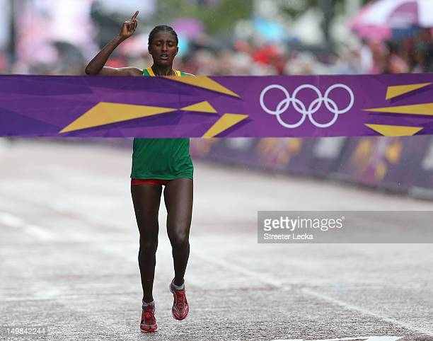 Tiki Gelana of Ethiopia celebrates as she crosses the finish line to win the gold medal in the Women's Marathon at The Mall on Day 9 of the London...