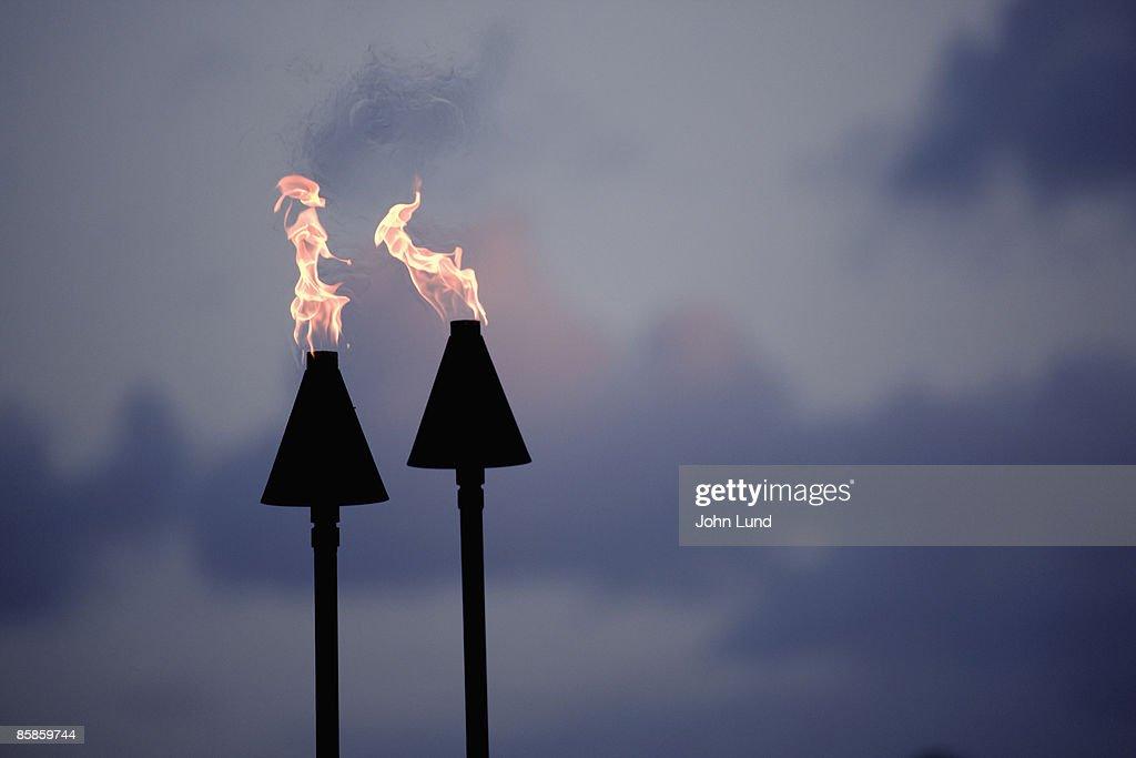 Tiki torches at Sunset : Stock-Foto