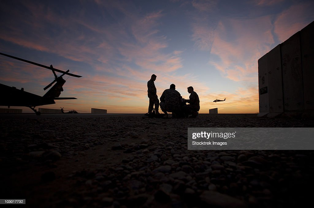 Tikrit, Iraq - A UH-60 Black Hawk crew carry out a mission brief at sunset. : Stock Photo