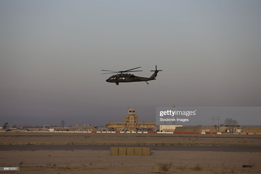 Tikrit, Iraq - A UH-60 Blackhawk helicopter flies past the tower on Camp Speicher. : Stock Photo
