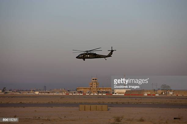 Tikrit, Iraq - A UH-60 Blackhawk helicopter flies past the tower on Camp Speicher.