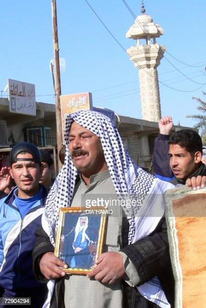 An Iraqi cries as he carries a portrait of executed former dicator Saddam Hussein during a demonstration in Saddam's hometown of Tikrit 30 December...