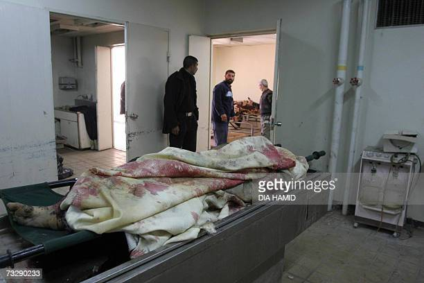 Iraqis look at the body of a victim as they stand at the entrance of the morgue of a hospital in the northern city of Tikrit 11 February 2007 A...