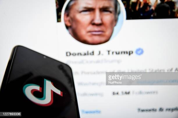 TikTok closeup logo displayed on a smartphone screen and the Twitter feed of the President of the USA, Donald Trump as background on a TV screen in...