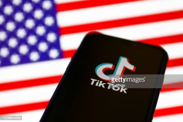 TikTok logo displayed on a phone screen is seen with American flag in the background in this illustration photo taken on September 21, 2020 in...