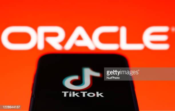 TikTok logo displayed on a phone screen is seen with Oracle logo in the background in this illustration photo taken on September 21, 2020 in Krakow,...