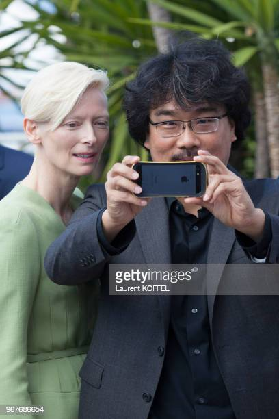 Tilda Swinton and director Bong JoonHo attend the 'Okja' Photocall during the 70th annual Cannes Film Festival at Palais des Festivals on May 19 2017...