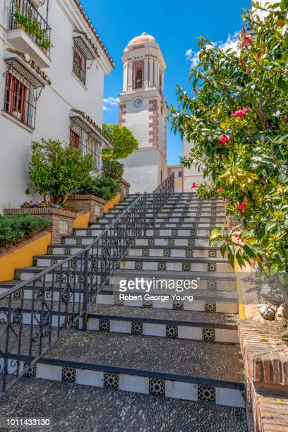 tile and aggregate stairway leads up to the estepona torre del reloj (clock tower). a 16th century bell tower, the only remnant of the original church. it stands in torre del reloj square. the belfry is 18th century neoclassical. - südeuropa stock-fotos und bilder