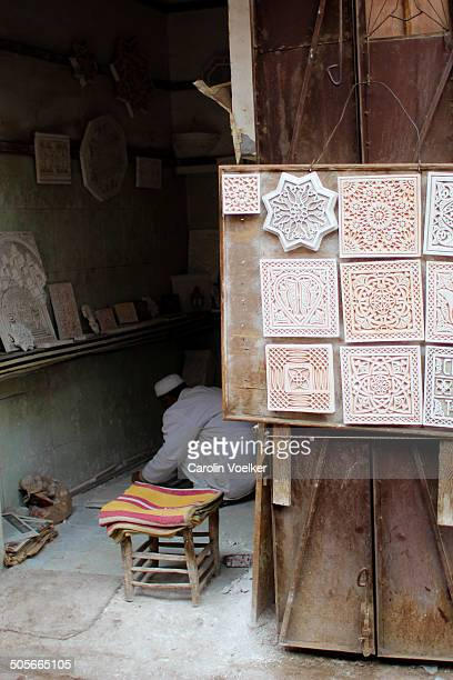 Tile maker in his workshop in Marrakech, Morocco. Some examples of his work are displayed on the wall outside.