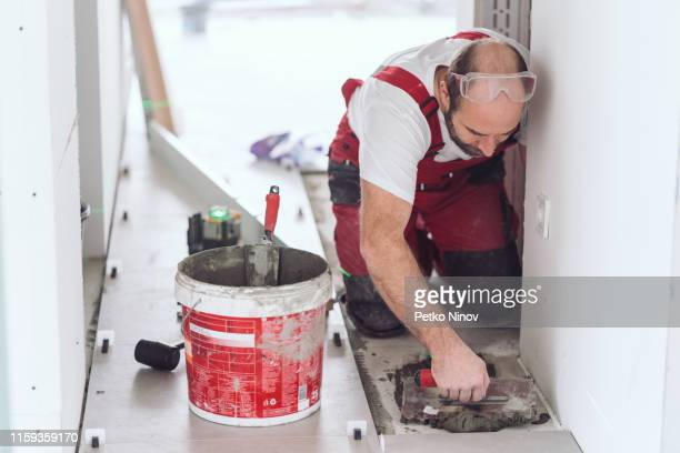 tile mason spreading tile adhesive on the floor - putting stock pictures, royalty-free photos & images