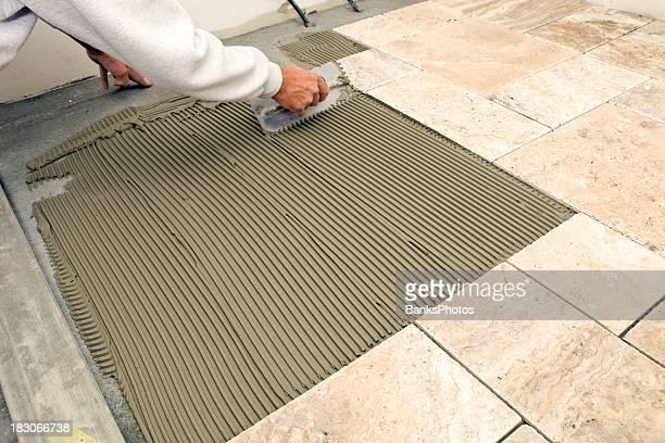 Carrelage Setter Troweling Pilon sur un sol de la salle de bains principale