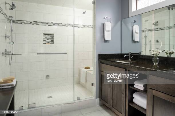 tiled modern bathroom with glass shower doors and steam shower - mirror steam stock photos and pictures