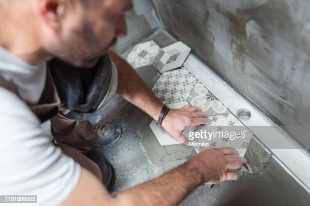 tiler installing tiles on the bathroom floor - tiled floor stock pictures, royalty-free photos & images