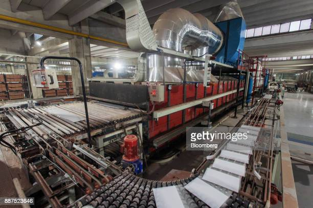 Tiles exit a kiln on a conveyor at the Shabbir Tiles Ceramics Ltd production facility in Karachi Pakistan on Wednesday Dec 6 2017 Shabbir which had...