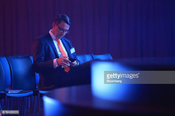Till Reuter chief executive officer of Kuka AG checks his smartphone before the start of the B20 Summit a business forum linked to Germany's G20...