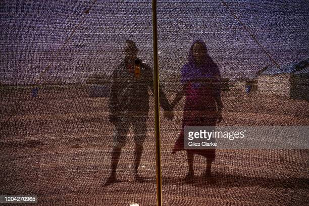 Tillaberi Refugee Settlement, Niger. December 13, 2019. A married refugee couple from Darfur stand on the scorched ground outside their shelter in...