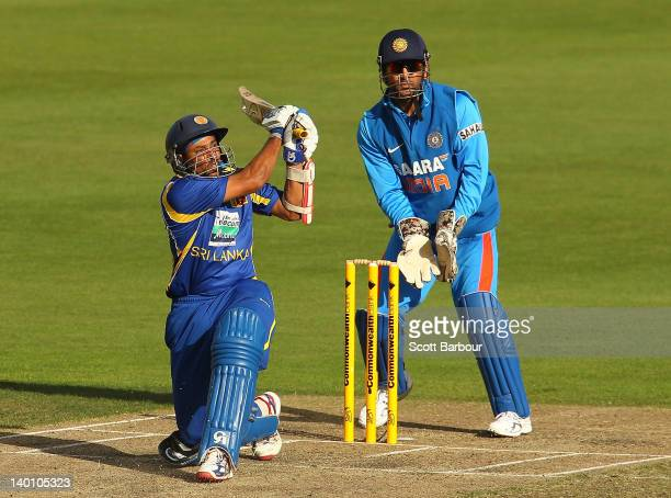 Tillakaratne Dilshan of Sri Lanka bats as wicketkeeper MS Dhoni of India looks on during the One Day International match between India and Sri Lanka...