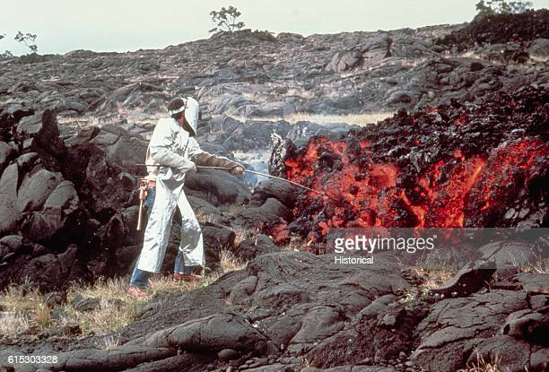 """Tilling takes a sample of molten """"Aa"""" lava from a flow on Mauna Ulu. He is wearing special clothing to protect him from the heat.   Location: Kilauea..."""