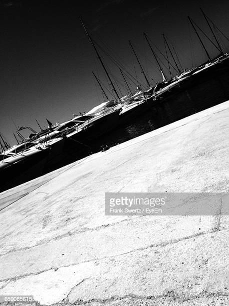 tilt image of boats moored at harbor against sky - frank swertz stockfoto's en -beelden