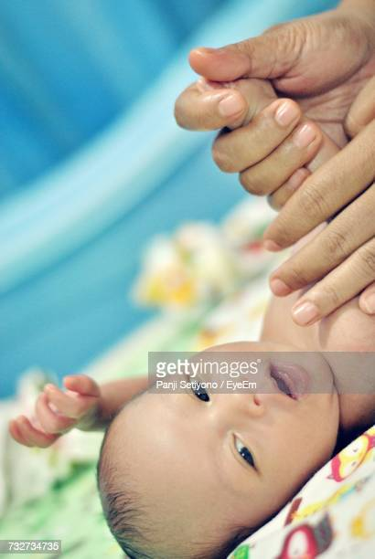 Tilt Image Of Cropped Hands Of Mother Massaging New Born Baby