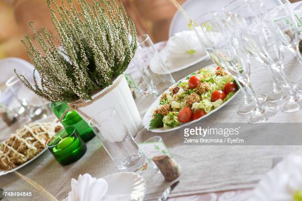 Tilt Image Of Food With Drinking Glasses And Plates By Potted Plant On Table