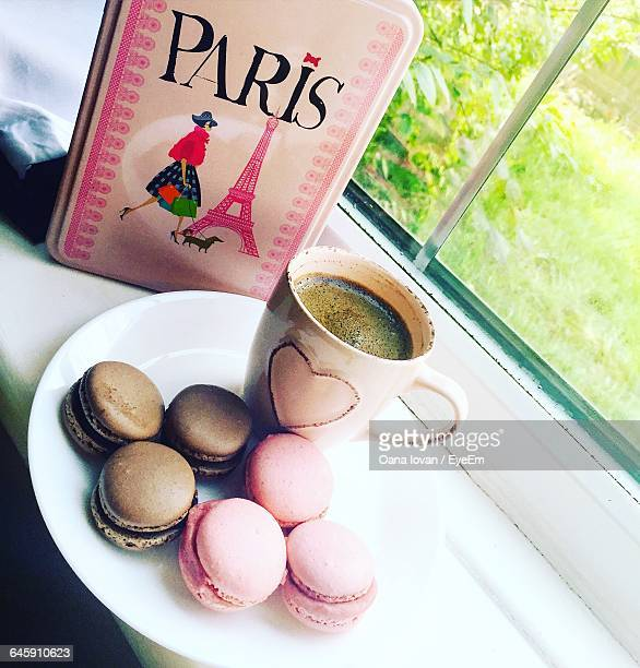 Tilt Image Of Macaroons With Coffee Served On Window Sill By Pink Bag