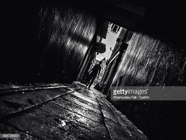 Tilt Image Of Man Holding Garbage Bag While Walking In Alley