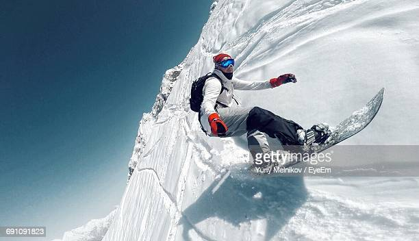 tilt image of man snowboarding against clear sky - boarding stock pictures, royalty-free photos & images