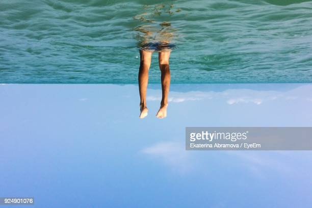 tilt image of man swimming in sea against sky - upside down stock pictures, royalty-free photos & images