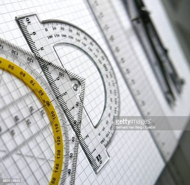 Tilt Image Of Set Square And Protractor With Drawing Compass By Ruler On Book