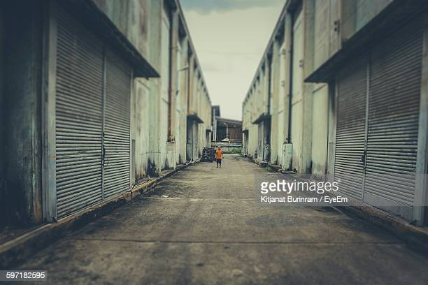 Tilt Shift Image Of Man Standing In Alley Amidst Buildings In City