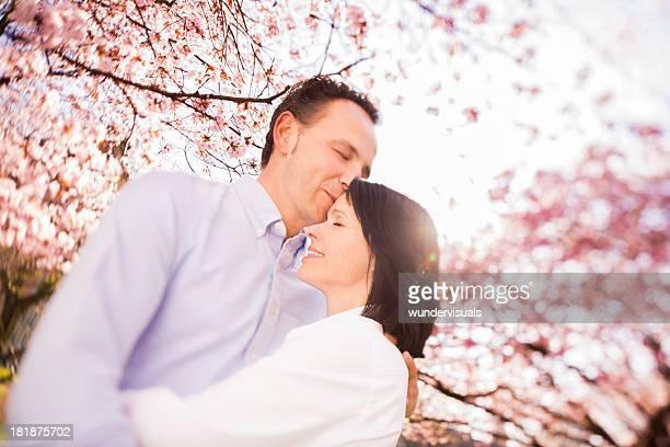 Tilt shift image of mature couple kissing under cherry blossoms