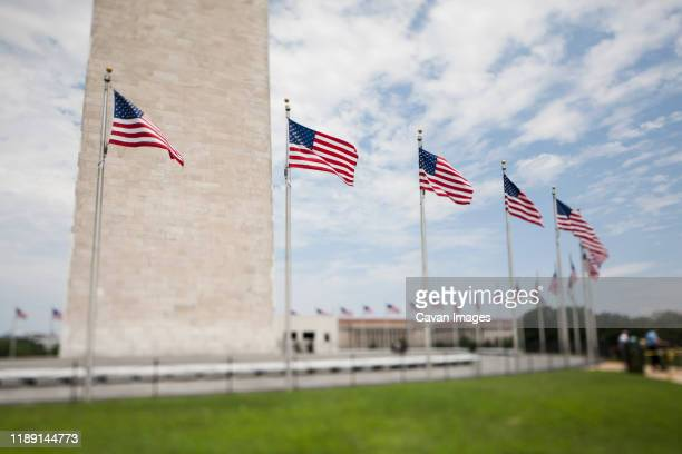 tilt shift view of flags beneath the washington monument in dc. - national monument stock pictures, royalty-free photos & images