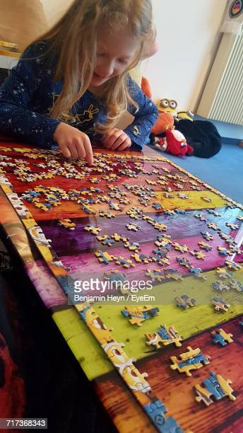 Tilt Shot Of Girl Playing Jigsaw Puzzle At Home