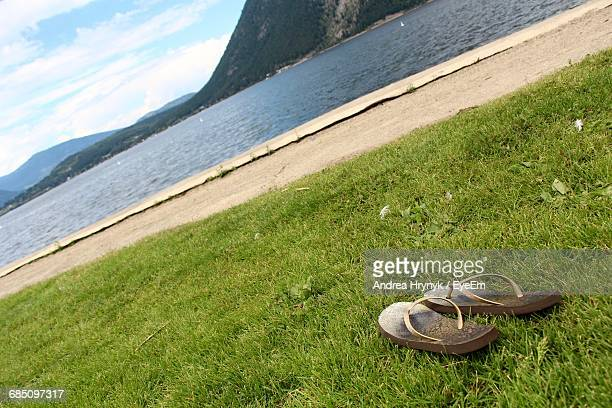 Tilt Shot Of Slippers On Grass On Shore Against Mountains