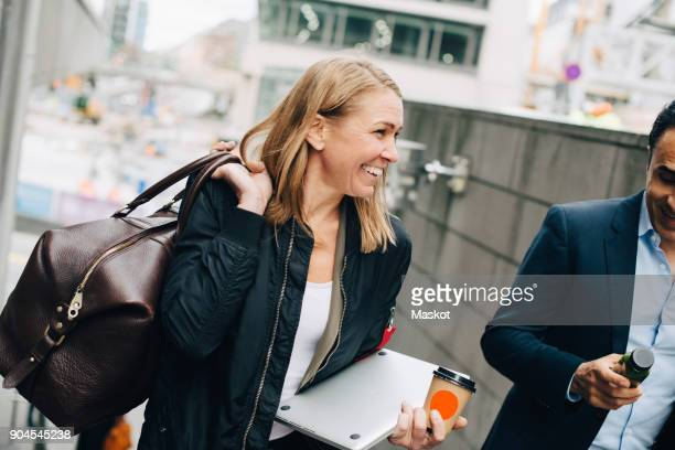 tilt shot of smiling mature business colleagues on staircase in city - business travel stock pictures, royalty-free photos & images